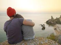 Romantiska unga bekymmerslösa par som kramar på en Cliff During Sunset Den tillbaka sikten av förälskad det fria för kvinnan och  Royaltyfri Bild
