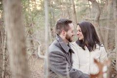 Romantiska unga par bara i skogen på en kall vinterdag royaltyfri fotografi