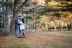 Romantiska unga par som kramar under ett träd på en kall nedgångdag royaltyfri fotografi