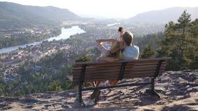 Romantiskt älska parsammanträde på träbänk och beundra staden och floden i dalen arkivfilmer