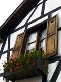 Romantiskt balkongfönster med blommor Arkivfoto