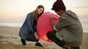 Romantiskt datum på stranden under solnedgång: Unga multietniska par som rymmer den röda pappers- lyktan, innan lansering arkivfilmer