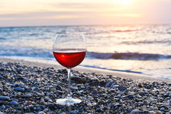 Romantiskt exponeringsglas av vinsammanträde på stranden på den färgrika solnedgången, exponeringsglas av rött vin mot solnedgång Royaltyfri Fotografi
