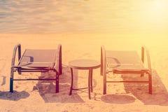Romantiskt feriesemesterbegrepp Par av soldagdrivare och en tabell på en öde strand med solen under solnedgång royaltyfri foto