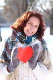 Romantiskt flickainnehav för söt vinter en röd hjärta utomhus Arkivfoton