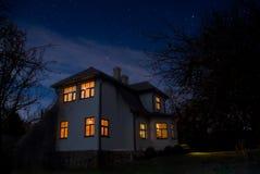 Romantiskt hus med ett ljus i fönstret Nattlandskap i sommar Royaltyfri Fotografi