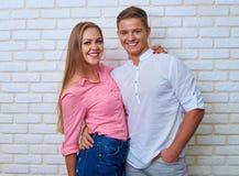 Romantiskt omfamna par som poserar på kameran över vita lodisar Arkivfoton