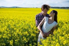 Romantiskt paranseende i senapsgult fält Fotografering för Bildbyråer