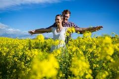 Romantiskt paranseende med armar som är utsträckta i senapsgult fält Royaltyfri Fotografi