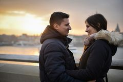 Romantiskt parsammanträde på en bro på solnedgången royaltyfria bilder
