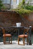 Romantiskt scenary, tabell med två stolar, två exponeringsglas av vin och en flaska av vin Arkivfoton