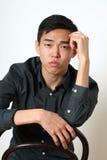 Romantiskt ungt asiatiskt mansammanträde på en stol Arkivbild