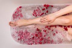 Romantiskt valentindagbad med rosa petails, kvinna i den hem- brunnsorten, lyxig självomsorg royaltyfria bilder