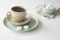 Romantyczna śniadaniowa scena z filiżanką i spodeczkiem, herbata, mennicy zieleni puchar z cukrowymi sześcianami zdjęcia royalty free
