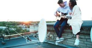 Romantyczna atmosfera, Piękna szczęśliwa para siedzi o nthe dach Przystojny facet bawić się gitarę i uroczy zdjęcie wideo