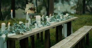 Romantyczna atmosfera Stół słuzyć dla dwa Liście, kwiaty, wielopoziomowy tort z jagodami i świeczki, są zakrywać zdjęcie wideo