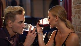 Romantyczna atmosfera wokoło ładnego mężczyzna i kobiety pije wino w restauraci i patrzeje each inny z pasją zbiory