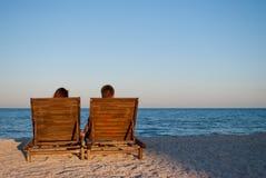 Romantyczna daktylowa dziewczyna i chłopak siedzimy na drewnianych deckchairs fotografia royalty free