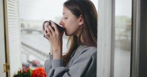 Romantyczna dziewczyna pije gorącego cappuccino i chłodzi zbiory