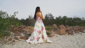 Romantyczna dziewczyna w długiej sukni na skalistym brzeg zbiory wideo