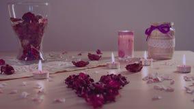 Romantyczna instalacja na stole: płonące świeczki, sercowaci kwiaty, garnka pourri zbiory