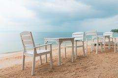Romantyczna kawiarnia z biel krzesłami na dennym brzeg i stołami obraz stock