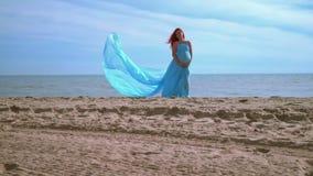 Romantyczna kobieta w błękit sukni na plaży gospodarstwa brzucha kobiety w ciąży zdjęcie wideo