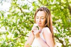 Romantyczna młoda kobieta z zamkniętymi oczami w wiosna ogródzie wśród jabłczanego okwitnięcia, miękka ostrość Fotografia Stock