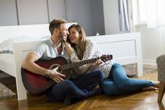 Romantyczna para bawić się gitarę na podłoga zdjęcia royalty free