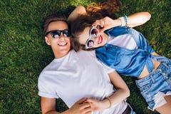 Romantyczna para młodzi ludzie w okularach przeciwsłonecznych kłama na trawie w parku Dziewczyna z długim kędzierzawym włosy kłam zdjęcia stock