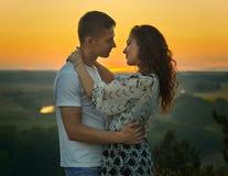 Romantyczna para patrzeje each inny przy zmierzchem na krajobrazie i jaskrawym żółtym niebie plenerowym, pięknym, miłości czułośc Obrazy Royalty Free