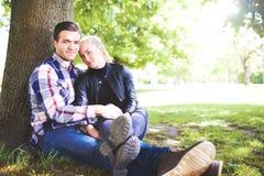 Romantyczna para przy Parkowym obsiadaniem Obok drzewa zdjęcia royalty free