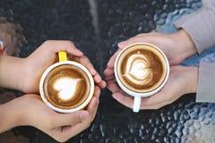 Romantyczna para trzyma dwa filiżanki latte sztuka z wzorem na stole w sklepie z kawą w miłości ręce serce zdjęcia stock