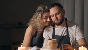 Romantyczna para w miłości pracuje wpólnie w rzemiosło pracownianym warsztacie i rysuje serce na glinianym garnku zbiory