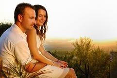 Romantyczna para z dziewczyny obsiadaniem na facecie przy zmierzchem obrazy royalty free