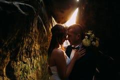 Romantyczna piękna panna młoda i elegancki elegancki fornal trzyma each inny w ciemniącej rockowej rozpadlinie backgrounded zmier Zdjęcie Royalty Free