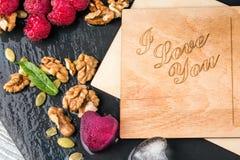 Romantyczna pocztówka Odgórny widok śliczna karta, lodowi serca, różowe jagody i orzechy włoscy na ciemnym tle, Walentynka dnia k Obraz Royalty Free