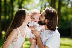 Romantyczna rodzina na na wolnym powietrzu Młoda ciemnowłosa kobieta i jej mąż całujemy ich powabnej małej córki zdjęcie royalty free