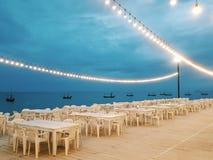 Romantyczna scena obiadowy miejsce z łomotać stoły, oświetleniowe żarówki, dennego widok i łodzi rybackiej tło, fotografia royalty free