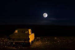 Romantyczna scena stary rocznika samochód z pary inside i księżyc na niebie przy nocą Sylwetka samochód na księżyc w pełni tle i  Fotografia Stock