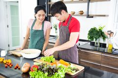 Romantycznej młodej uroczej pary kulinarny jedzenie w kuchni zdjęcia stock