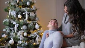 Romantyczni momenty, dziewczyna siedzą na leżance i przytulenie mężu blisko jedlinowy drzewo na wigilii boże narodzenia zbiory