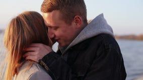 Romantyczni para stojaki w uściskach i buziakach each inny przy jeziorem zdjęcie wideo