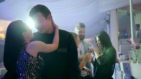 Romantyczni para stojaki zamknięci na tle jaskrawi światła w klubie wpólnie zbiory