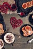 Romantyczny śniadanie Dwa filiżanki kawy, cappuccino z czekoladowymi ciastkami i ciastka blisko czerwonych serc na drewnianym sto Obrazy Stock