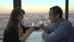 Romantyczny świętowanie na hotelu tarasie, kochankowie mówi i ono uśmiecha się, otuchy z szampanem, w górę miasto widoku, piękny  zdjęcie wideo