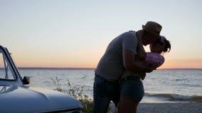 Romantyczny buziak na natury blisko wodzie, lata potomstwa odpoczynek dobiera się na brzeg rzece na zmierzchu, spotkanie szczęśli zbiory