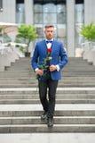 Romantyczny d?entelmen Mężczyzny dojrzały ufny macho z romantycznym prezentem Przystojnego facet róży kwiatu romantyczna data Wal obrazy royalty free