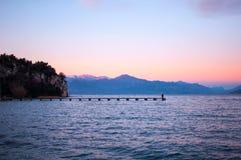 Romantyczny fiołkowy zmierzch na jeziorze z długim molem i ludźmi wal Zdjęcie Royalty Free
