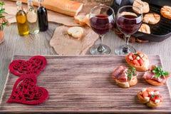 Romantyczny gość restauracji Miłość Bruschetta ustawiający dla wina z pomidorami, prosciutto, ziele i olejem na drewnianej desce, Zdjęcie Royalty Free